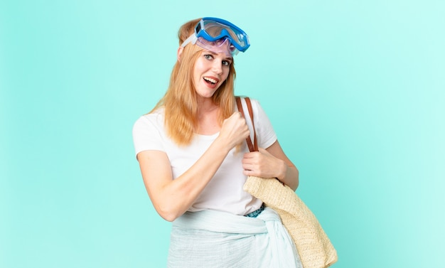 Pretty red head woman feeling happy and facing a challenge or celebrating with goggles. summer concept