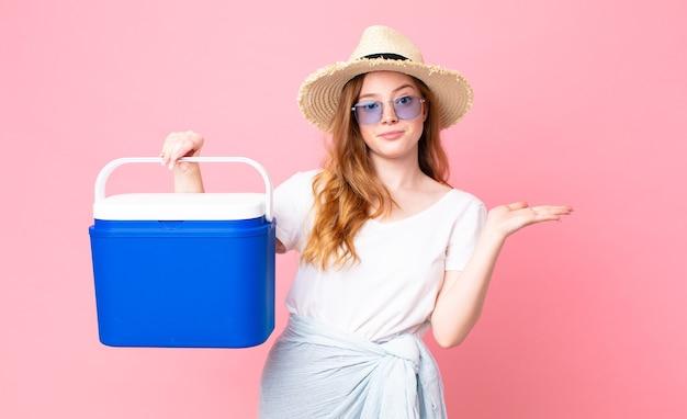 예쁜 빨간 머리 여자는 어리둥절하고 혼란스럽고 의심하고 피크닉 휴대용 냉장고를 들고 있습니다.