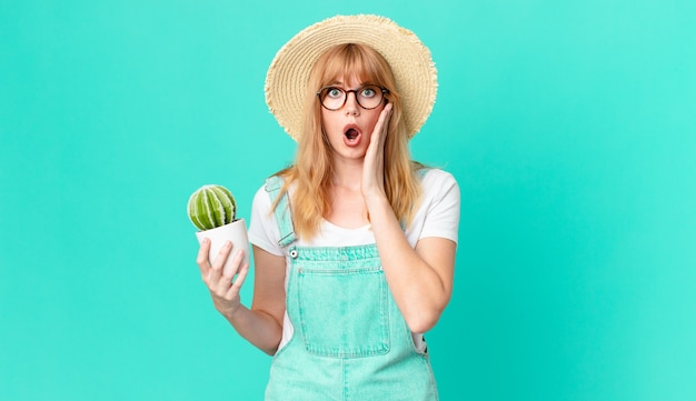 ショックを受けて怖がって、鉢植えのサボテンを持っているかなり赤い頭の女性。農家のコンセプト