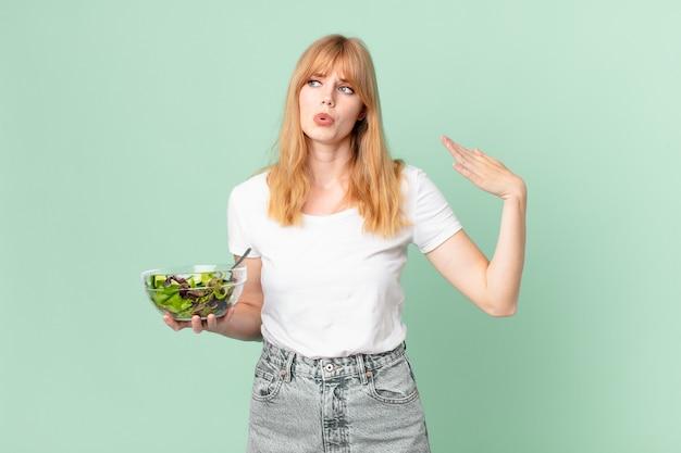 Довольно рыжая женщина чувствует себя подчеркнутой, взволнованной, усталой и разочарованной и держит салат. концепция диеты