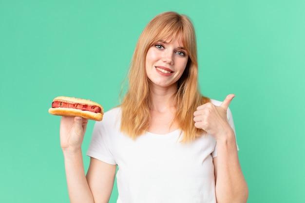 ホットドッグを持っているかなり赤い頭の女性。