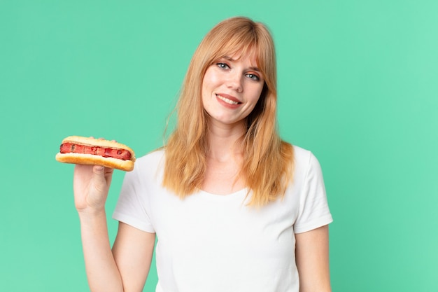 Pretty red head woman holding a hot dog.