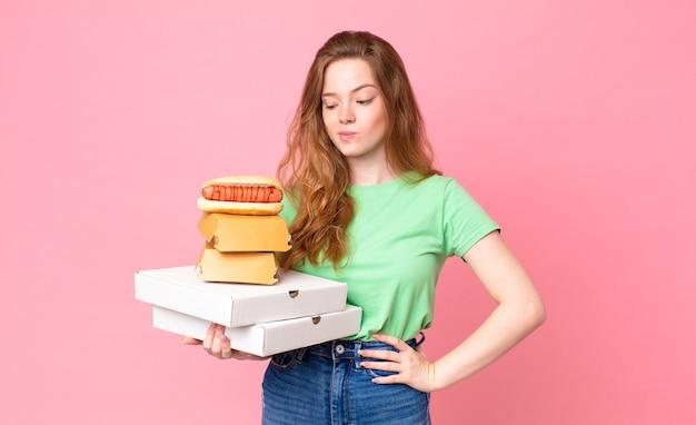 Довольно рыжая женщина, держащая коробки быстрого питания на вынос