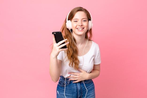 Довольно рыжая женщина громко смеется над веселой шуткой в наушниках и смартфоне