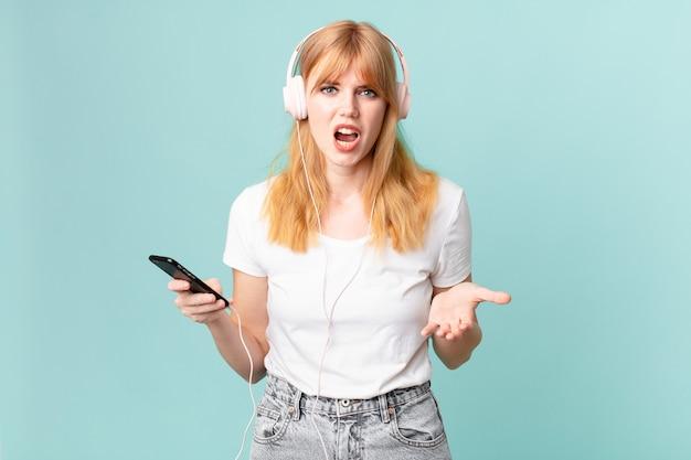 Довольно рыжая женщина выглядит сердитой, раздраженной и разочарованной и слушает музыку в наушниках
