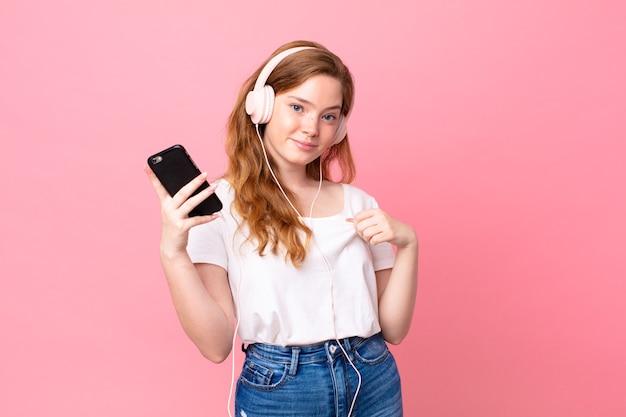 Довольно рыжая женщина выглядит высокомерной, успешной, позитивной и гордой в наушниках и смартфоне