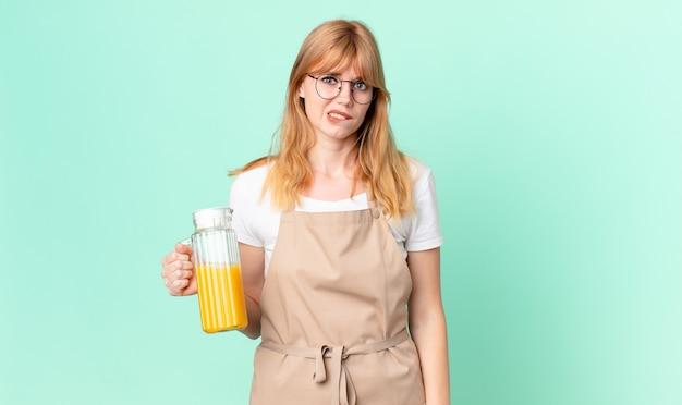 オレンジジュースを準備しているエプロンと困惑して混乱しているように見えるかなり赤い頭の女性