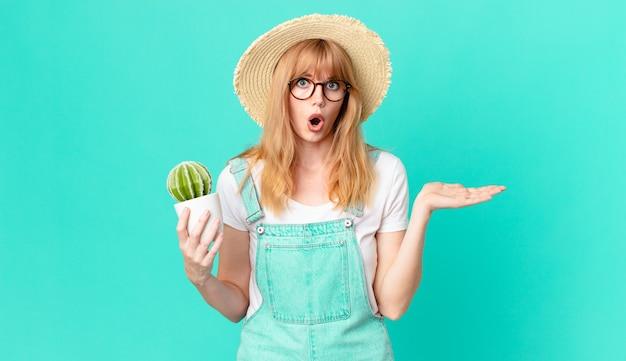 かなり赤い頭の女性が驚いてショックを受けたように見え、顎を落とし、物を持って鉢植えのサボテンを持っていました。農家のコンセプト
