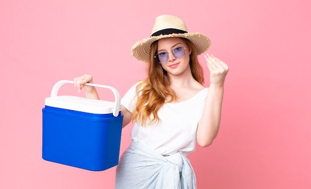 Pretty red head woman making capice or money gesture, telling you to pay and holding a picnic portable refrigerator