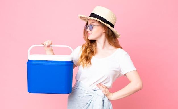 프로필 보기에 예쁜 빨간 머리 여자 생각, 상상 또는 공상을 하고 피크닉 휴대용 냉장고를 들고