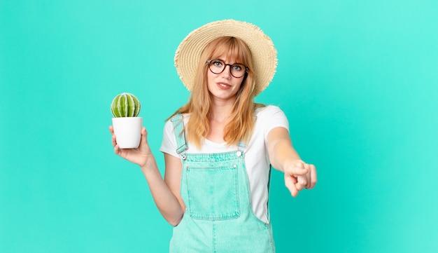 あなたを選んで、鉢植えのサボテンを持っているカメラを指しているかなり赤い頭の女性。農家のコンセプト