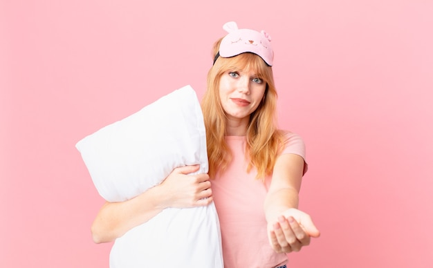 예쁜 빨간 머리 여자가 친절하게 웃으며 개념을 제공하고 보여줍니다. 잠옷을 입고 베개를 들고