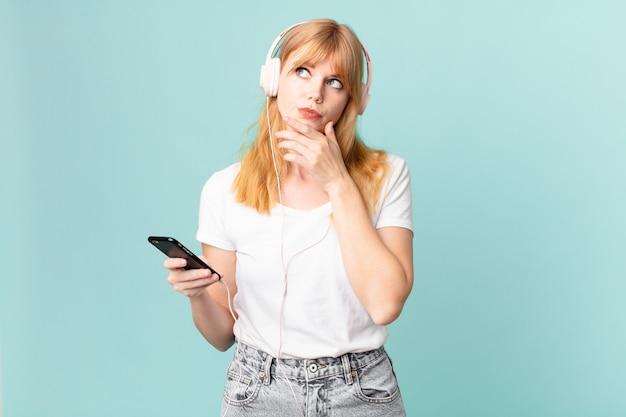 Довольно рыжая женщина думает, сомневается и смущается и слушает музыку в наушниках