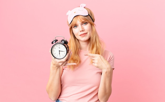 잠옷을 입고 알람 시계를 들고 꽤 빨간 머리 여자. 일어나 개념