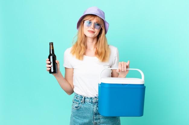 휴대용 냉장고와 맥주를 가진 예쁜 빨간 머리 여자