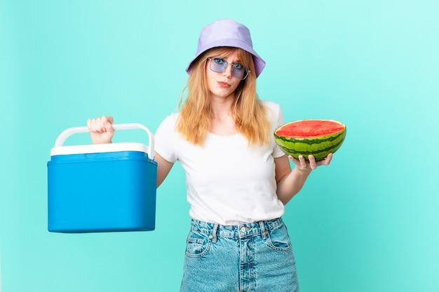ポータブル冷蔵庫とスイカを持つかなり赤い頭の女性