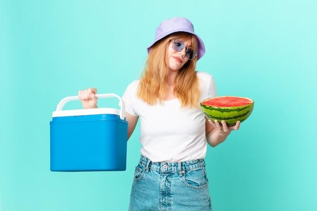 휴대용 냉장고와 수박을 가진 예쁜 빨간 머리 여자