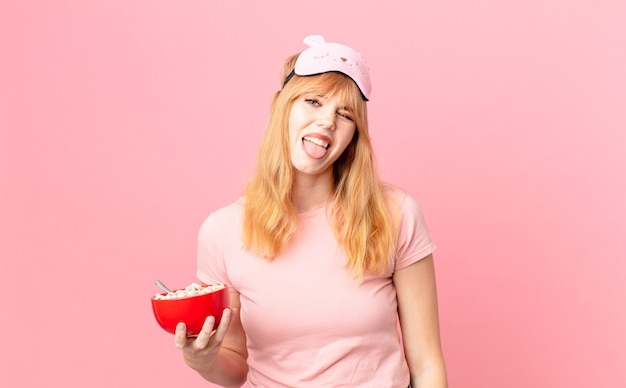 Pretty red head woman with cheerful and rebellious attitude, joking and sticking tongue out wearing pajamas and holding a flakes bowl