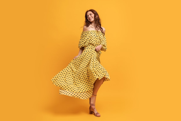 Pretty red-head woman in yellow dress posing on yellow. summer mood