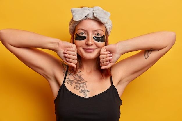かなりリデッドの女性は目の下にパッチを適用し、くまのアイマスクを着用し、ヘッドバンドと黒いシャツを着て、肌と顔色のポーズを気にします