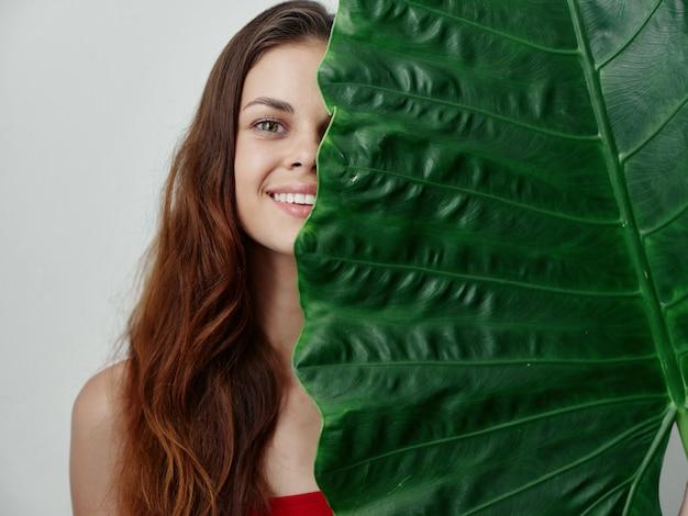 かなりredhaired女性は緑のヤシの葉のクローズアップで葉の半分をカバーしています