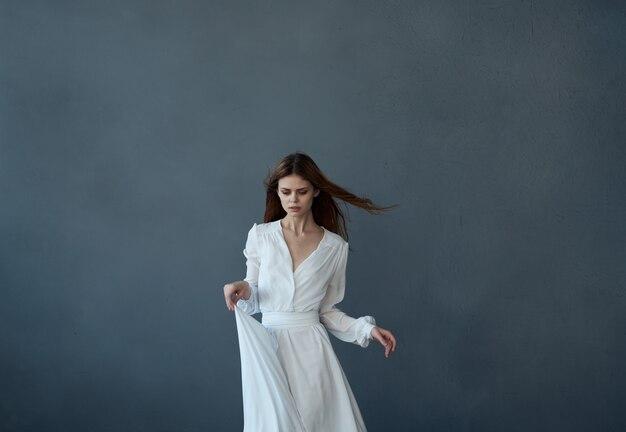 하얀 드레스를 입은 예쁜 redhaired 여자 재미있는 댄스 어두운 배경