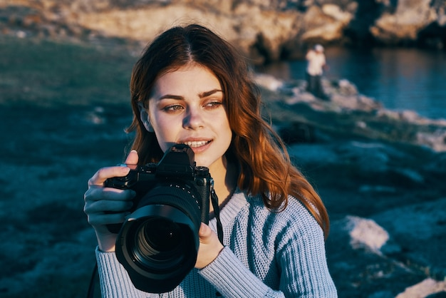 Pretty redhaired woman photographer in nature landscape freedom vacation