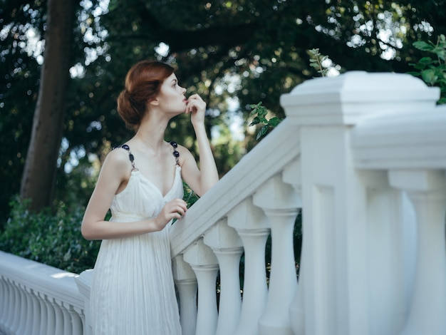 Pretty redhaired woman in white dress posing in the park mythology