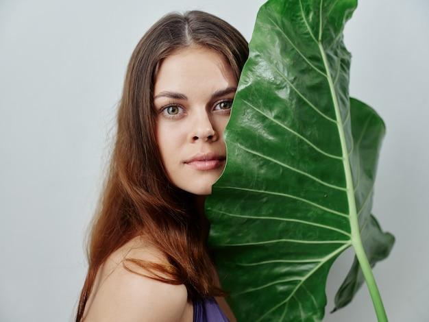 水着で緑のヤシの葉を持つかなりredhaired女性