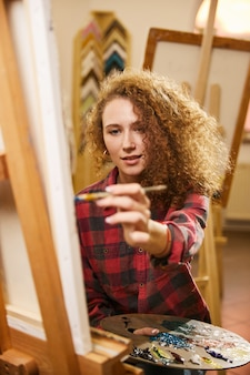 Pretty redhead curly artist with smile draws a painting