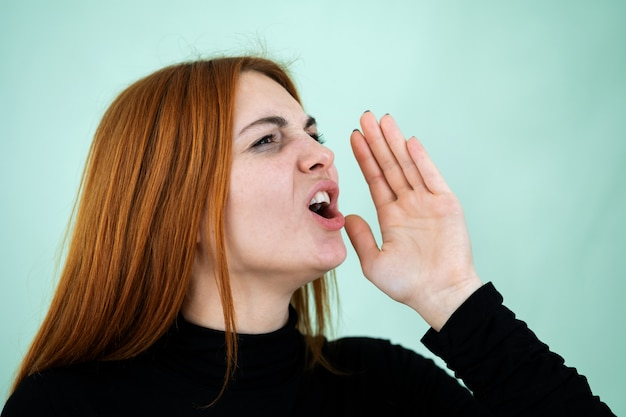 Pretty redhead girl shouting loudly holding her palm to face.