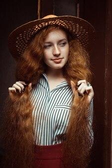 古い木製のドアの近くでポーズをとる麦わら帽子の長い巻き毛のかわいい赤毛モデル