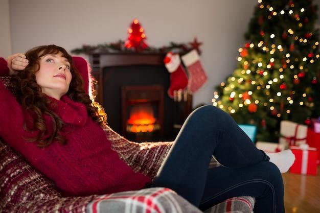 Pretty redhead sitting on armchair thinking