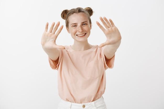 Ragazza adolescente bella rossa che propone contro il muro bianco