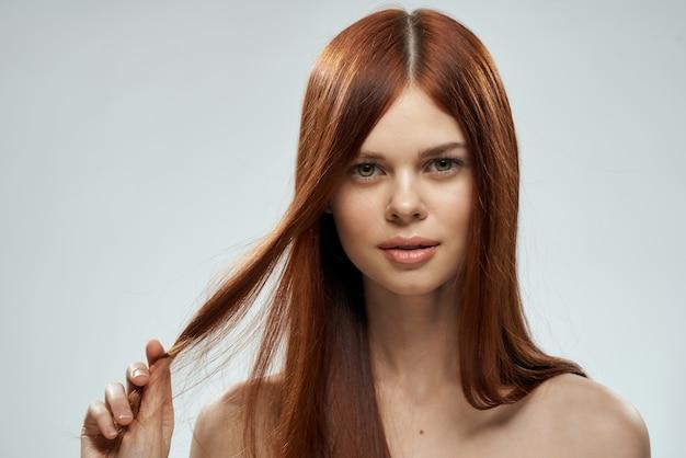 Довольно рыжая женщина, держащая ее волосы на светлом фоне.