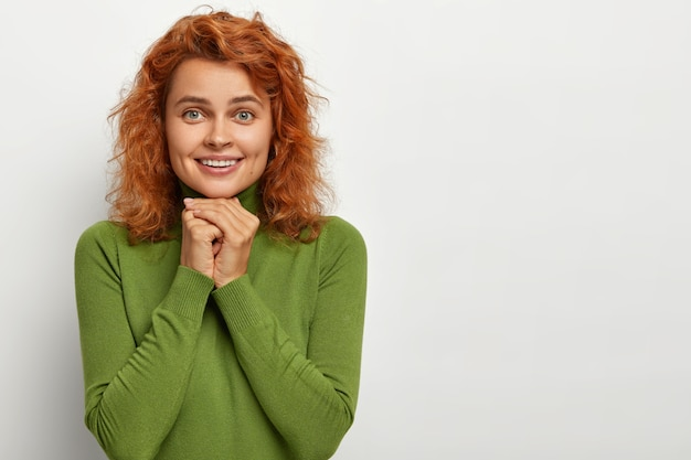 예쁜 빨간 머리 여자는 사랑스러운 표정으로 보이고, 매혹적인 모습을 가지고 있으며, 턱 근처에서 손을 함께 누르고, 평온한 삶을 행복하게 살고, 캐주얼 한 녹색 점퍼를 입고, 흰 벽에 서서, 빈 공간