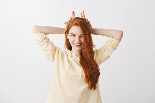 かなりの赤毛の女性が偽の角を示し、幸せな笑顔