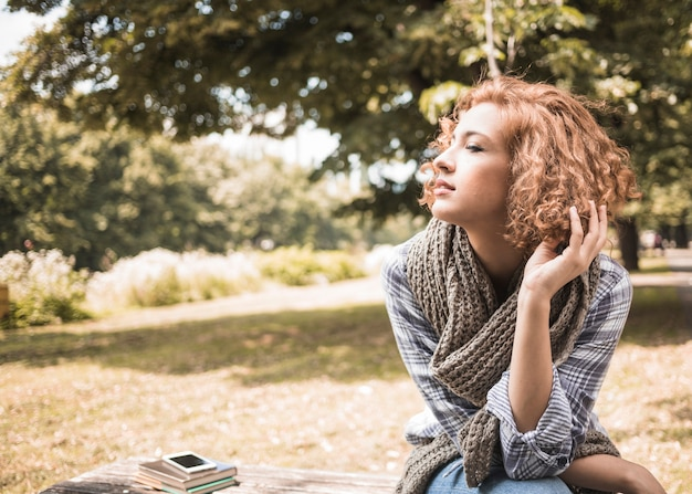 Pretty redhead woman sitting on bench in park