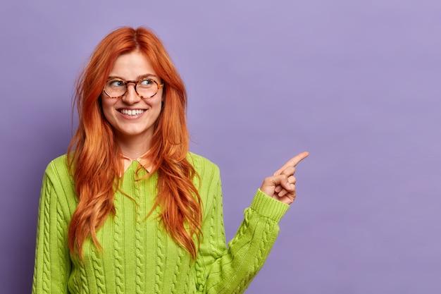 이빨 미소로 예쁜 빨간 머리 여자는 복사 공간에 멀리 포인트