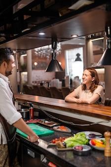 Симпатичная гостья ресторана сидит за стойкой и спрашивает шеф-повара о меню на открытой кухне