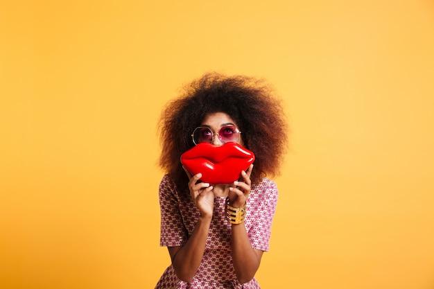 Pretty retro stylish african woman having fun while posing with big red lips, looking upward