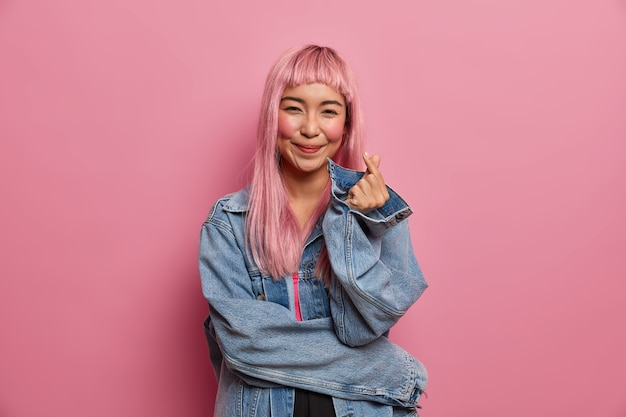 Donna asiatica abbastanza romantica con un sorriso carino amore, lunghi capelli rosa, fa segno di dito cuore coreano, esprime amore e simpatia, confessione