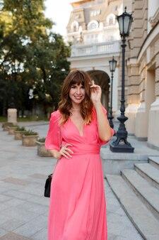 Довольно романтичная женщина в розовом платье позирует на открытом воздухе в старой европе.