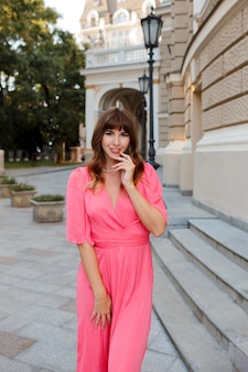 Pretty romantic woman in pink dress posing outdoor in old european ity.