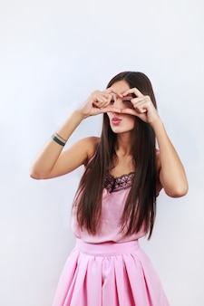 Pretty romantic young indian woman making a heart gesture with her fingers in front of her chest showing her love