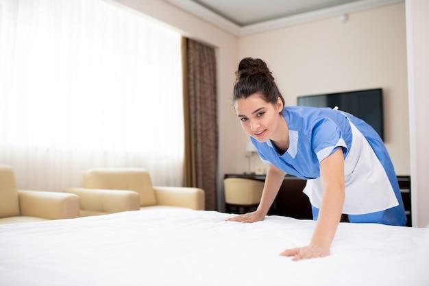 ホテルで働きながら午前中にベッドを作る青い制服と白いエプロンのかわいい部屋のメイド