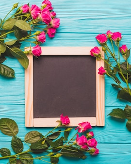 Pretty roses near chalkboard