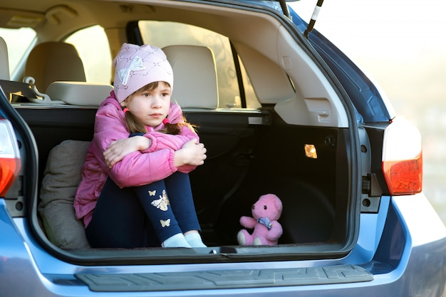 Pretty sad child girl sitting alone in a car trunk with a pink toy teddy bear.