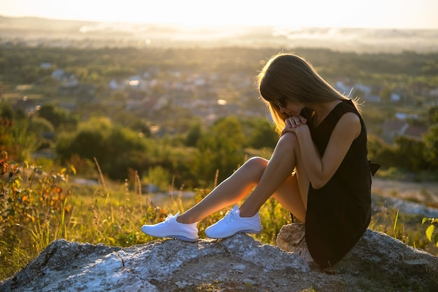 Pretty sad woman in black short summer dress sitting on a rock thinking outdoors at sunset. fashionable female contemplating in warm evening in nature.