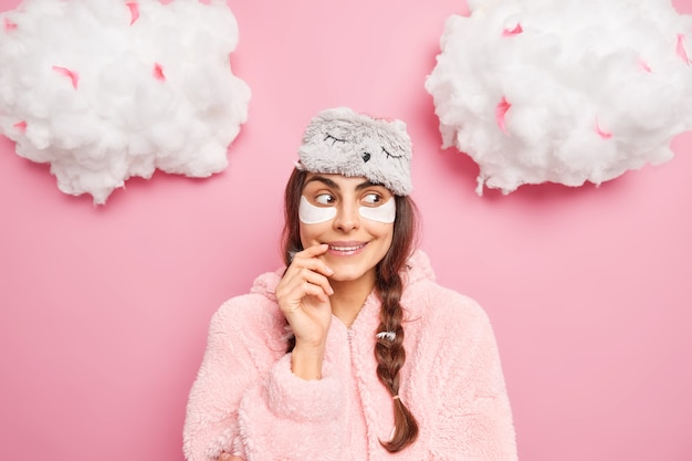 Pretty satisfied european girl smiles gently has curious face expression enjoys comfort and serene atmosphere at home wears sleepmask with pajama isolated over pink wall going to sleep